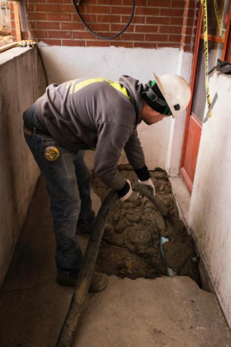 Travailleur coulant du ciment pour remettre la fondation à niveau