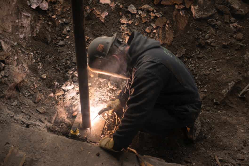 Un travailleur soudant des piliers d'acier à des plaques d'acier pour étayer une fondation