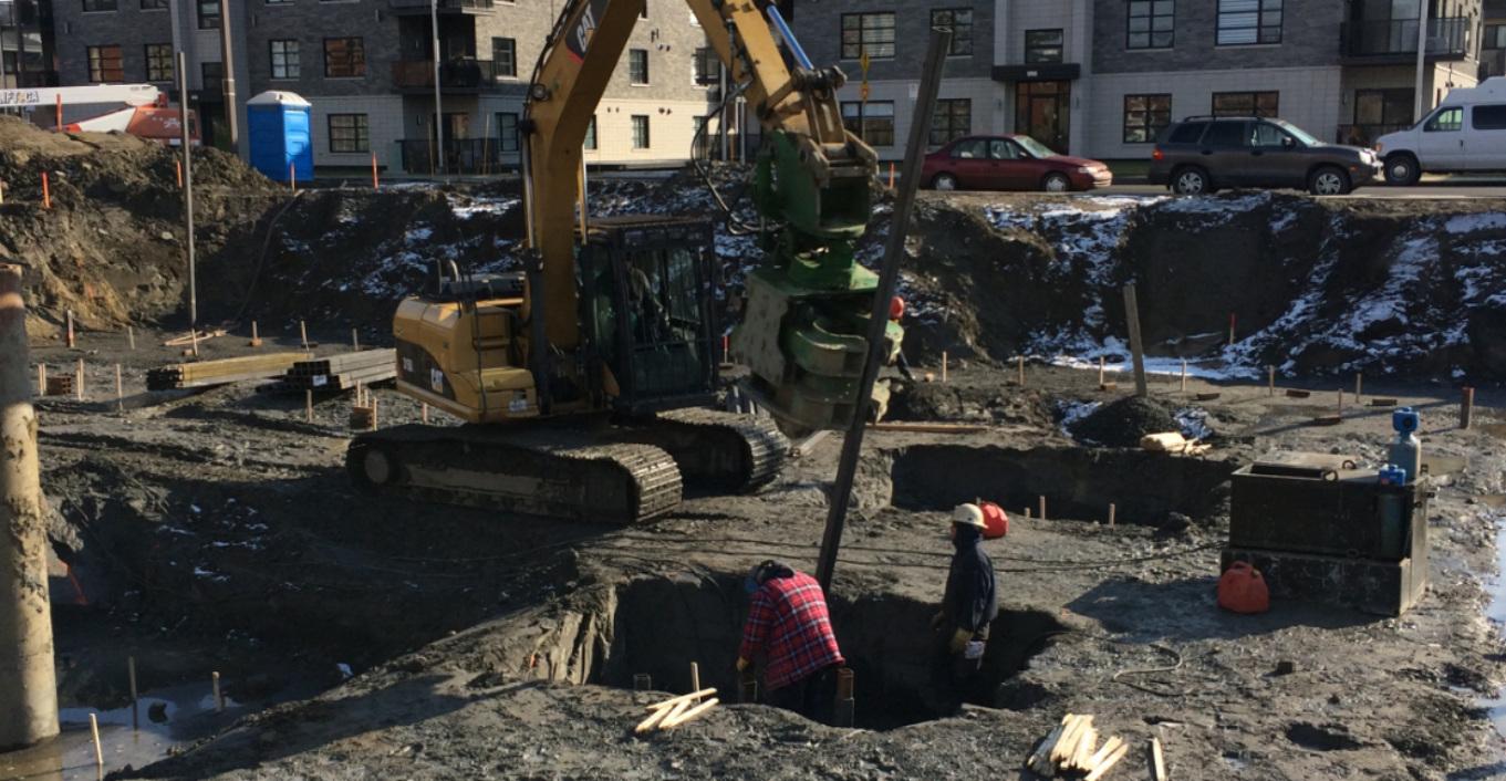 Travailleurs préparant l'équipement pour enfoncer les pieux d'acier dans le sol par vibration