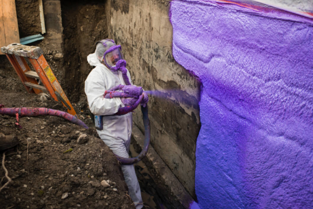 A worker applying waterproofing membrane