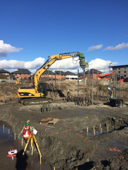 Machinery vibrating the steel piles into the ground